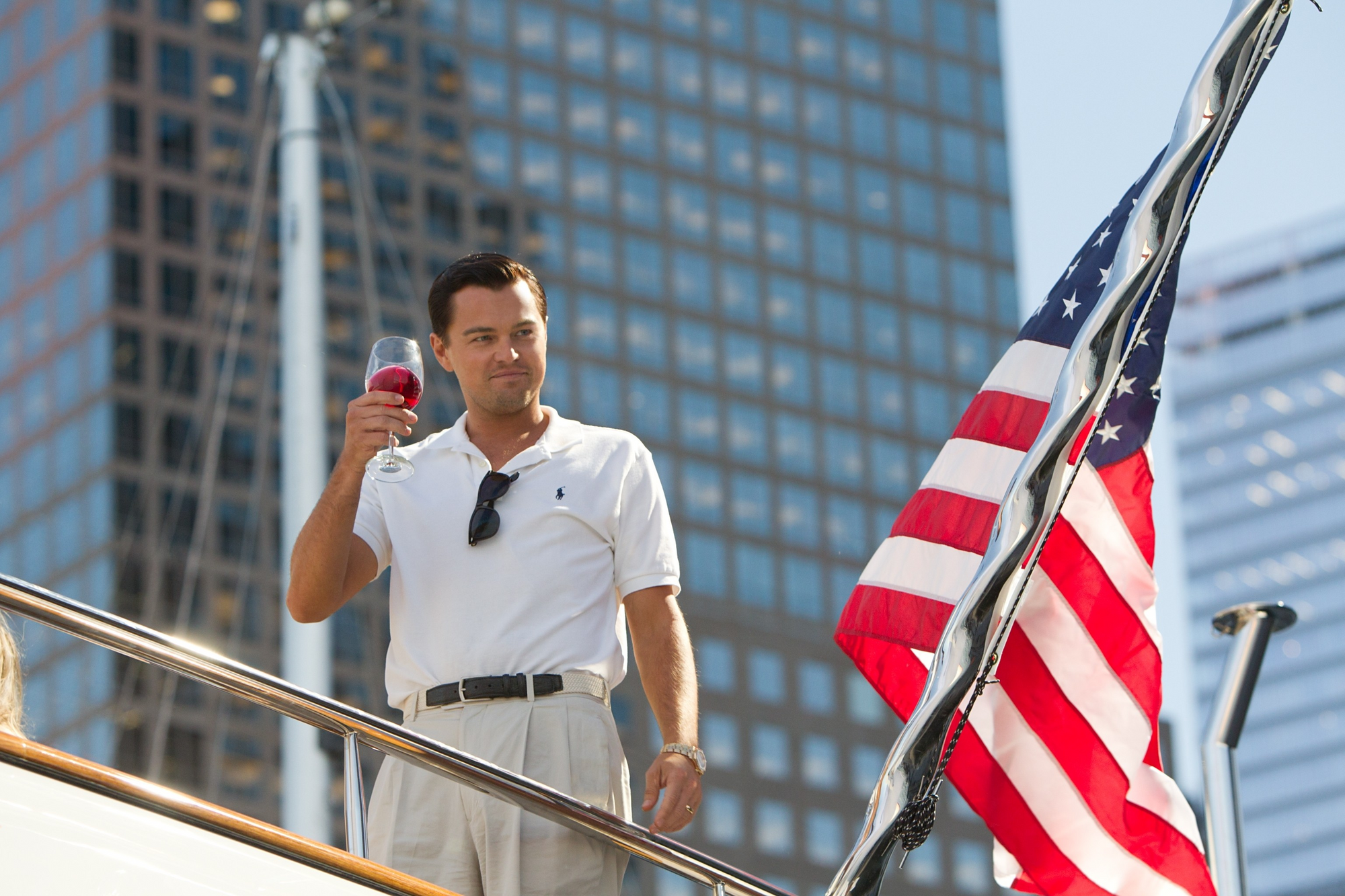 Jordan Belfort on his yacht holding a glass of red wine