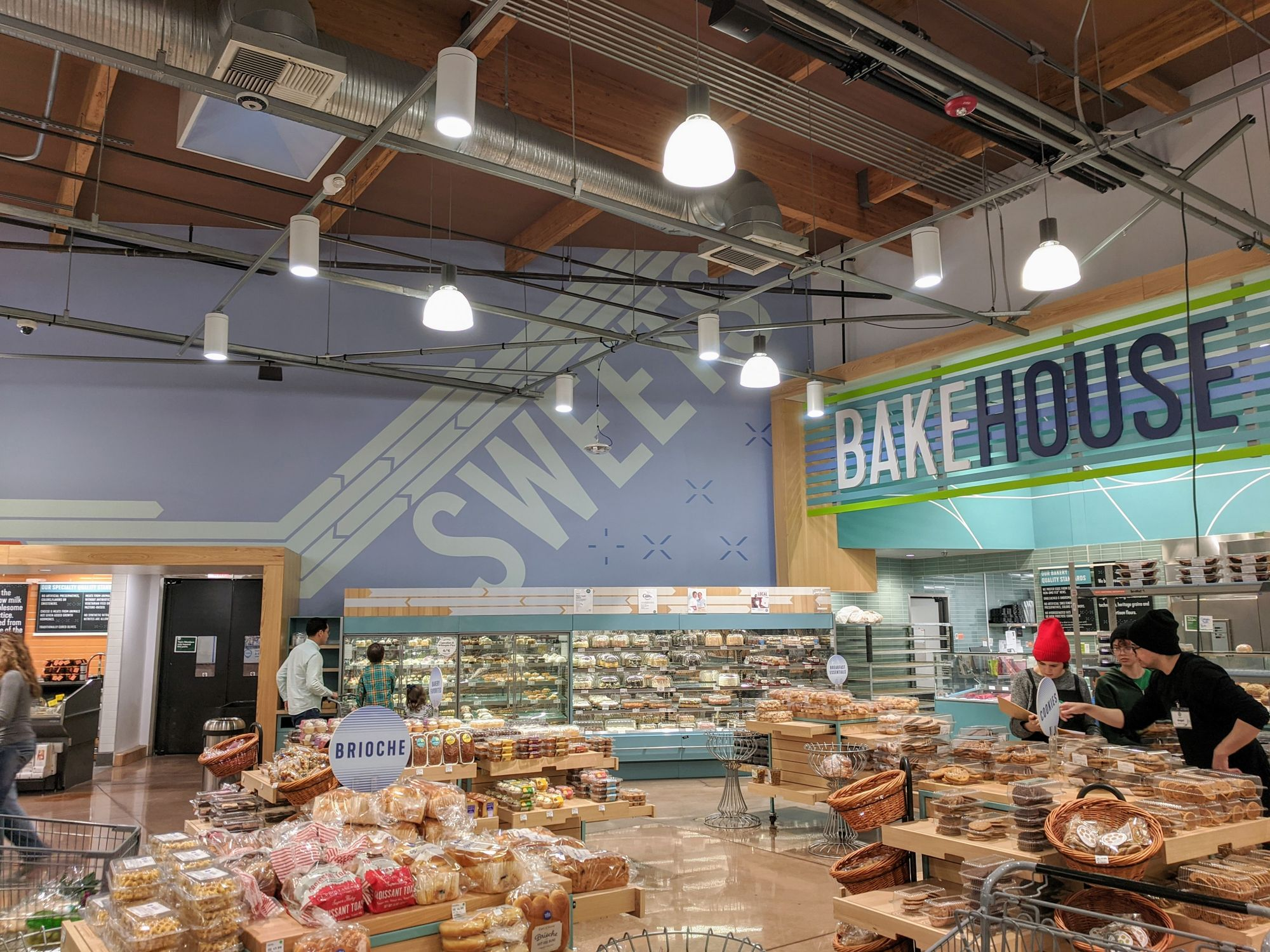 """The bakery section of Whole Foods. Big typography on the wall says """"SWEETS""""."""